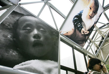 A South Korean woman wipes tears as she looks at pictures of starved North Korean children in Seoul.