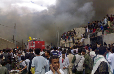 People watch as firefighters work at the scene of a fire at a market place in Sanaa