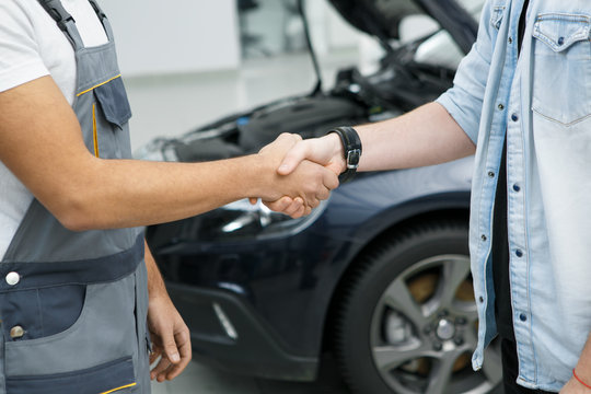 Auto repair shop mechanic shaking hands with his customer at the garage