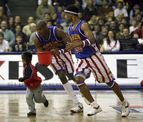 Dwayne Simpson of Harlem Globetrotters chases team mate Herbert Lang and a Turkish boy during exhibition game with NY Nationals in Istanbul