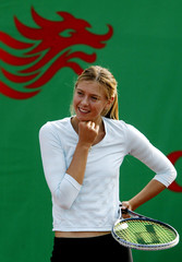Maria Sharapova of Russia gestures in front of a dragon symbol, an official logo of Hong Kong, durin..