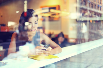 Cafe city lifestyle woman on phone drinking coffee texting text message on smartphone app sitting indoor in trendy urban cafe. Cool young modern mixed race Asian Caucasian female model in her 20s.