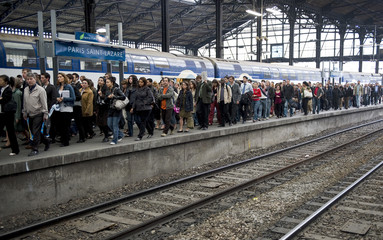 Commuters walk at Gare Saint Lazare train station in Paris during the strike by French SNCF railway workers