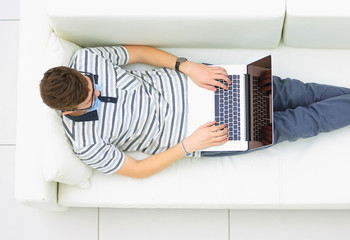 Man Relaxing on Sofa with Laptop Computer