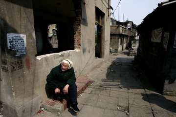 A resident sits near her home in a housing area designated for demolition by the government in Putuo district, Shanghai