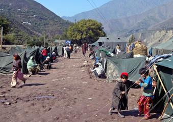 Kashmiri earthquake survivors sit outside their tents in Kalgai