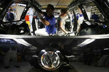 Volkswagen employees work on VW Passat at construction line of Volkswagen plant in Emden