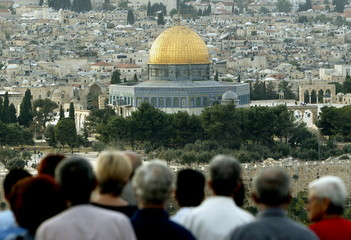 Tourists stand on the Mount of Olives overlooking the Old City of Jerusalem with the golden Dome of ..