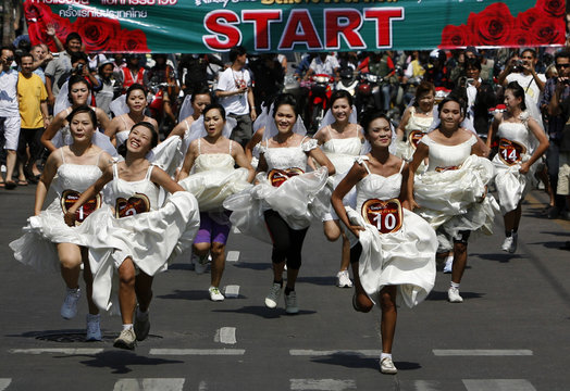 """Brides run after the start of the """"True Love... Fears No Distance"""" race on Valentine's Day in Pattaya"""