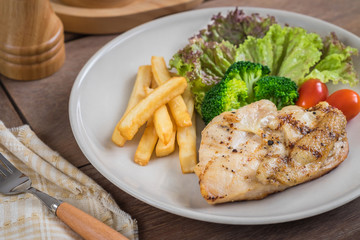 Grilled chicken steak and french fries on plate