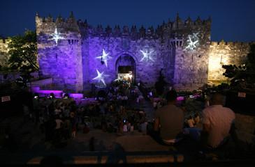 People sit near Damascus Gate in Jerusalem's Old City during the Jerusalem Festival of Lights