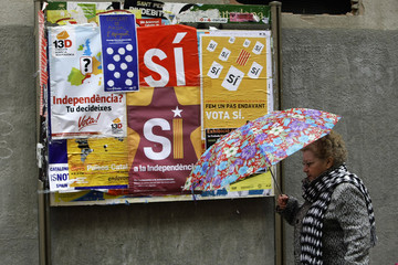 A woman walks past posters promoting an informal referendum in Vilafranca del Penedes