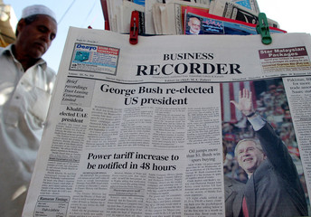 A Pakistani reads a newspaper headlining U.S. President George W. Bush's re-election victory at a ...