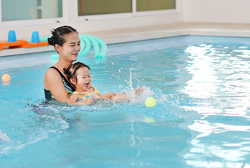 happy smiling asian little girl with mother swimming at water pool.