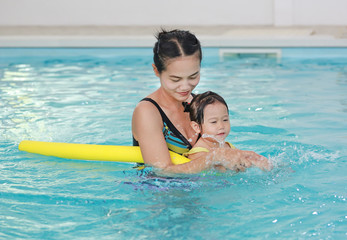 Happy smiling asian little girl with mother learning to swim with pool noodle