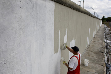 A worker plasters the rear side of the East Side Gallery the largest remaining part of the former Berlin Wall in Berlin