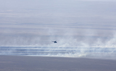 Rescue helicopter flies over smoke after Soyuz capsule landed in northern Kazakhstan