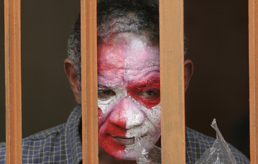 A Peruvian inmate with his face painted as a joker watches from behind bars after a ceremony marking Resocialization Day at Castro Castro prison in Lima