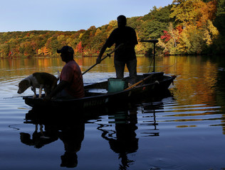 Two men and a dog are silhouetted on a boat as they head to shore on Lake Tiorati in Harriman State Park in New York