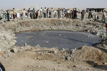 Residents gather around a crater after a bomb attack near Mosul