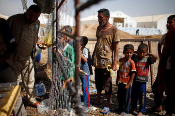 Displaced Iraqis wait for food supplies at Hammam al-Alil camp south of Mosul