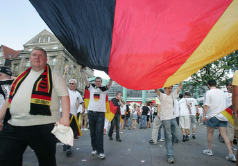 Soccer fans of Germany carry huge national flag before the World Cup soccer match between Germany and Italy in Dortmund