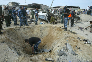 PALESTINIAN POLICEMEN SEARCH THE SCENE AFTER A BLAST BY AN APPARENTROADSIDE BOMB IN THE GAZA STRIP.