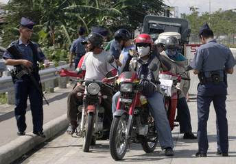 Police officers check motorcyclists' identification papers in Cebu