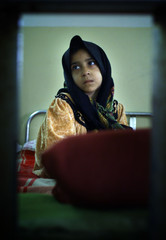 IRAQI SICK GIRL SITS ON HER BED IN BASRAH'S HOSPITAL.