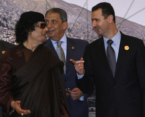Libya's leader Muammar Gaddafi chats with Arab League Secretary-General Amr Moussa and Syrian President Bashar al-Assad during Arab Summit in Damascus