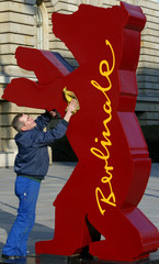 A worker cleans a huge mock-up of the Berlin bear award advertising the upcoming 55th International ...