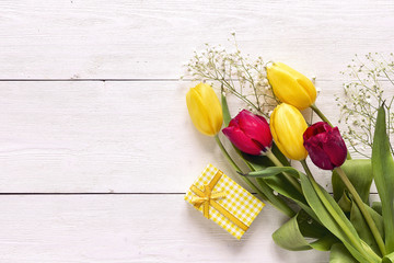 Bouquet of tulips with gift box on white wooden background.