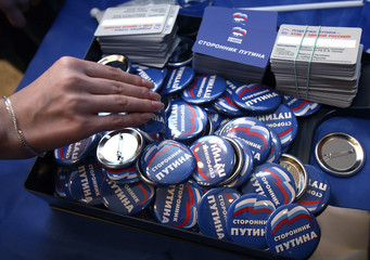 A participant takes a badge with Putin's Supporter written on it before the start of Vladimir Putin supporters forum in Russia's Siberian city of Krasnoyarsk