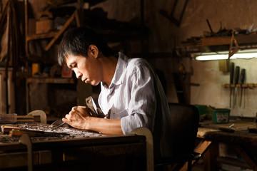 Man engraving in workshop