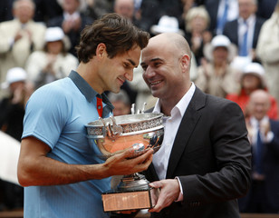 Federer is congratulated by former tennis champion Agassi after winning the men's final at Roland Garros in Paris