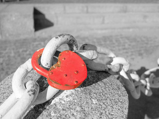 Red lock on a white chain on a black and white background