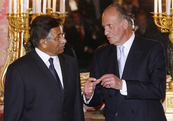 Pakistan's President Pervez Musharraf listens to Spain's King Juan Carlos before their dinner at the Royal Palace in Madrid