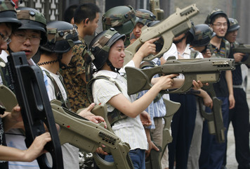 "Customers of Xuelang Outdoor Sports Club prepare laser guns for a ""Counter-Strike"" game in Beijing"
