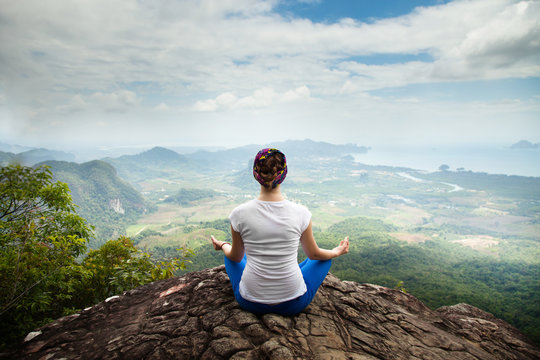 Young blonde woman practicing yoga and meditation in mountains during luxury yoga retreat in Bali, Asia