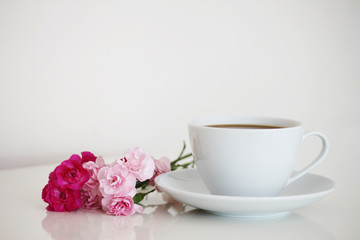 Cup of tea on white isolated background with flowers next to it