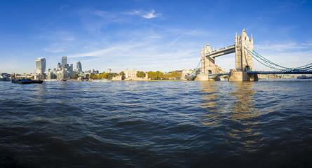 Bright scenic panorama of the London city skyline with Tower Bridge from the bank of the River Thames