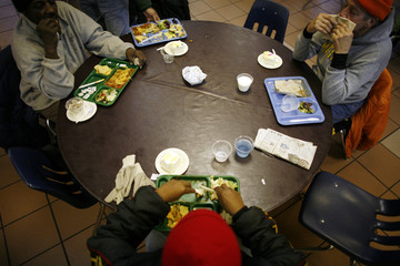 People eat lunch at the Capuchin Soup Kitchen, where hundreds of people receive food and supplies everyday, in Detroit