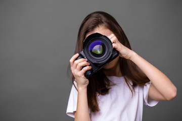 Cute brunette little girl holding an photo camera
