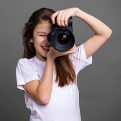 Cute brunette little girl holding an photo camera