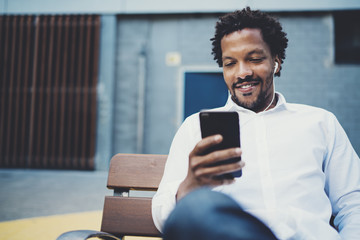 Young smiling african man using smartphone to listen to music while sitting on the bench at sunny street.Concept of happy handsome people enjoying gadgets outside.Blurred background.