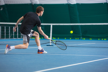The young man in a closed tennis court with ball