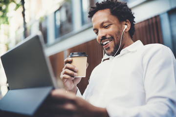 Happy African American man in earphones making video call via electronic touch pad with take away coffee in hand.Concept of guy using Internet-enabled electronic device outside.Blurred background.