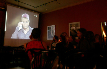 People watch Natascha Kampus' TV interview in a cafe in Vienna