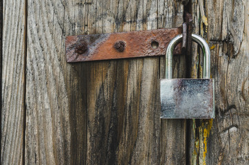 Metal padlock on a rustic wooden door