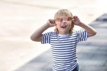 Pretty little boy on a skate board. Emotional kid outdoors. Cute child skating wearing sunglasses.